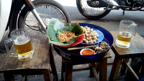 Two beers and platter of food on a table on a street corner