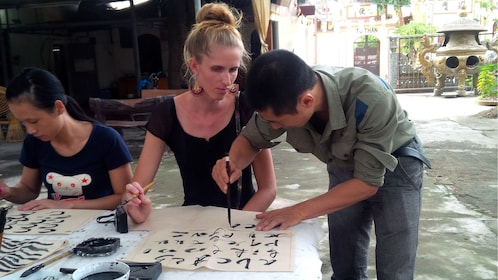 A woman learns vietnamese calligraphy on the street with an instructor