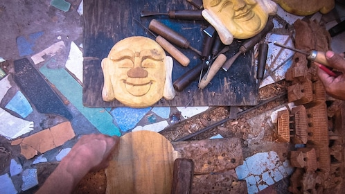 Above view of wood carvings in progress with tools.