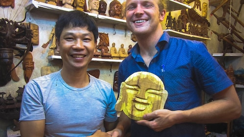 Smiling visitor with completed wood carving with teacher.