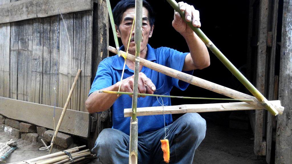 A man builds a bird trap out of sticks