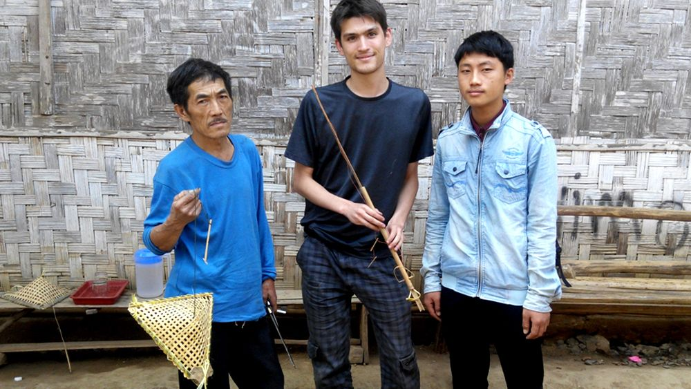 Three men pose with a finished woven bird trap