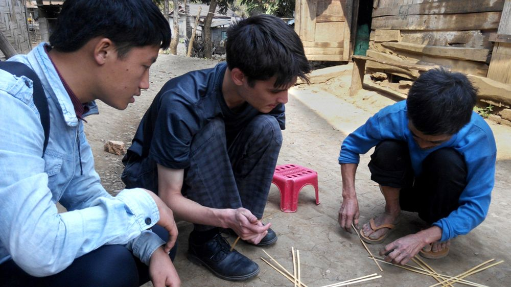 Three men squat next to bird trap supplies