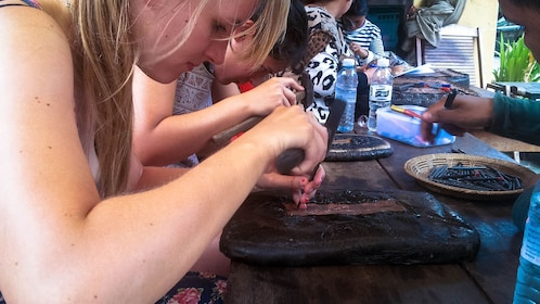 Tourists at a table creating jewelry out of copper with tools.