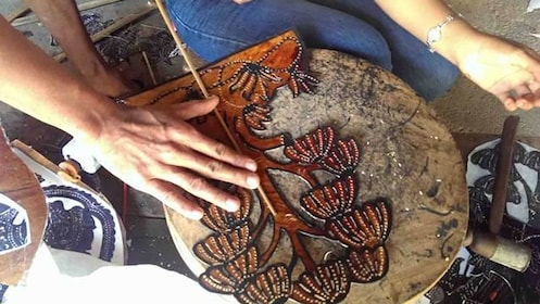 Leather worker is carving a tree design into leather