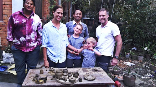 Family of four posing with two pottery instructors among their new creations