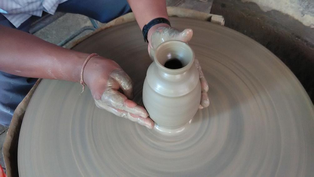 Show item 1 of 5. Medium shot of potter working on vase