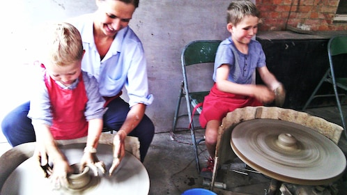 Mom and two young sons 'throwing' on pottery wheel
