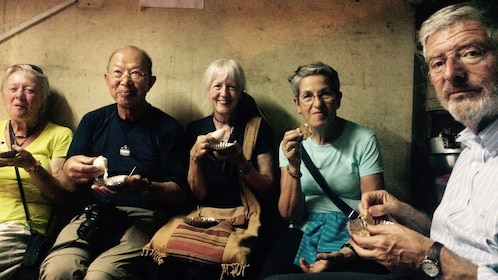 Group of five adults sampling the street food of Nepal
