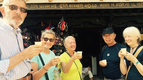 Group of five adults sampling hot nepalese tea