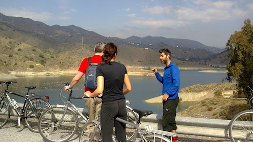 Cyclists observing landscape from a distance.