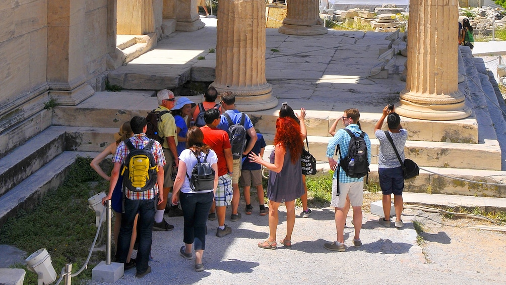 Tour group in Athens next to some columns