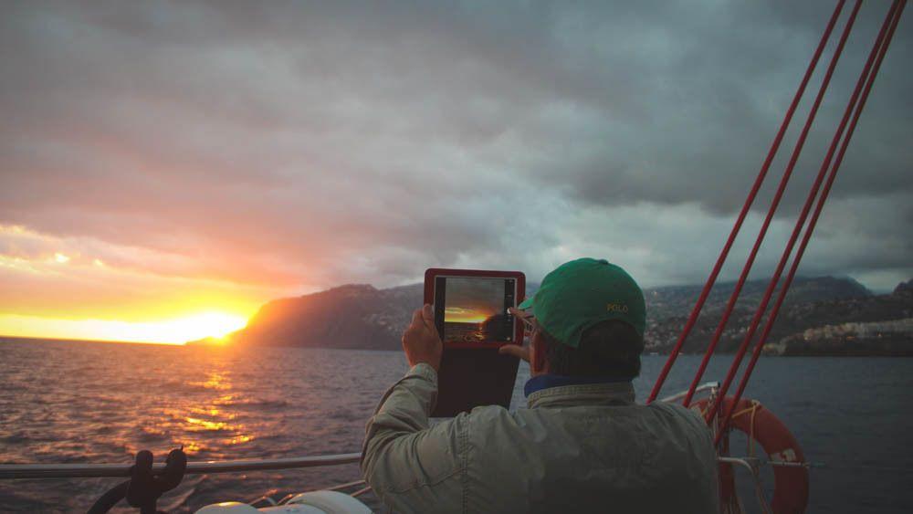 Man on boat taking photos of sunset.