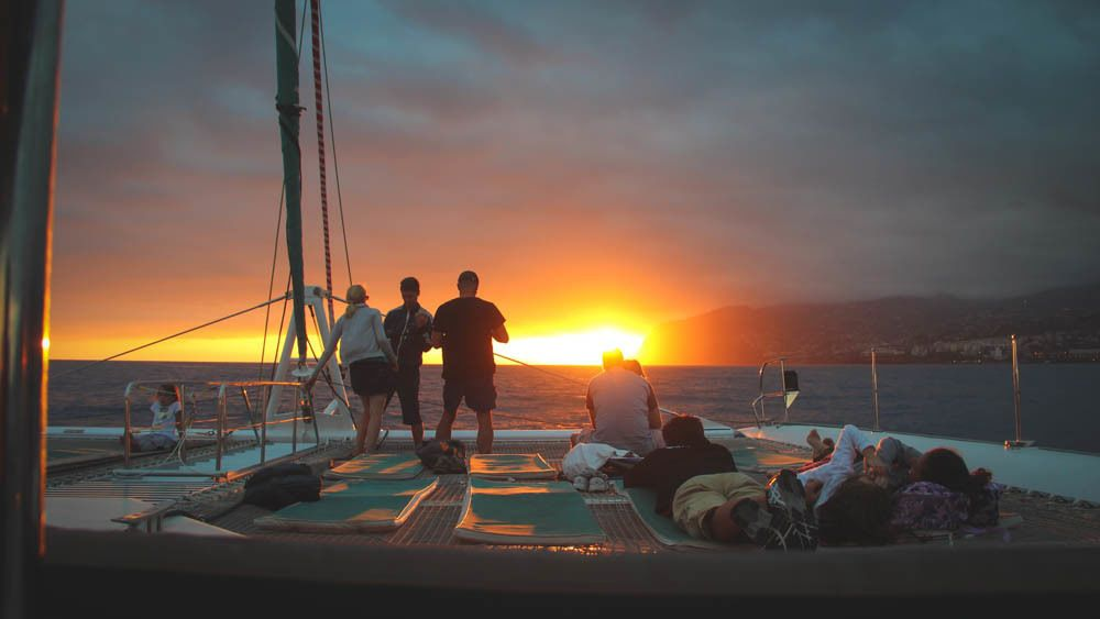 Group of people observing beautiful sunset on boat.