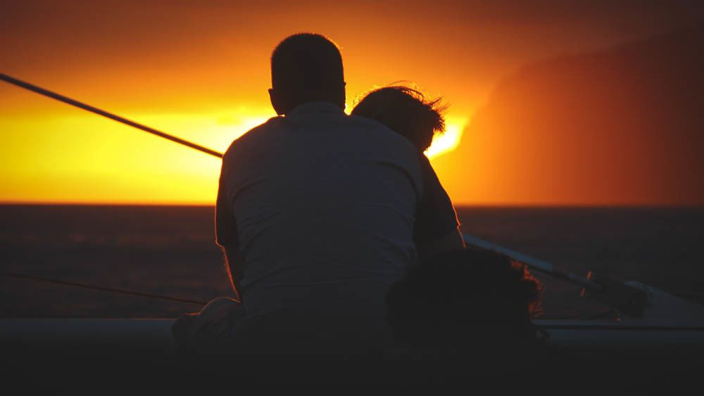 Couple embracing on a boat watching pretty sunset.