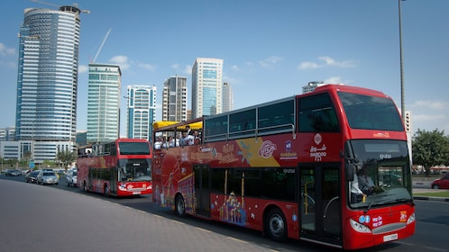 two double decker touring buses driving through the streets of Dubai