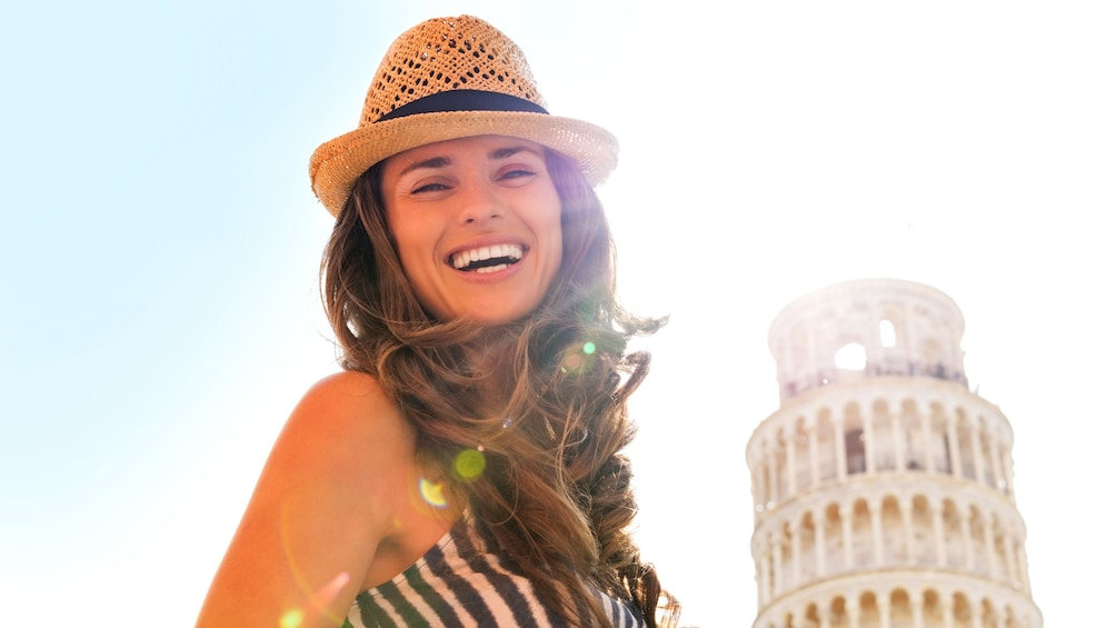 Woman smiling in front of Pisa building.