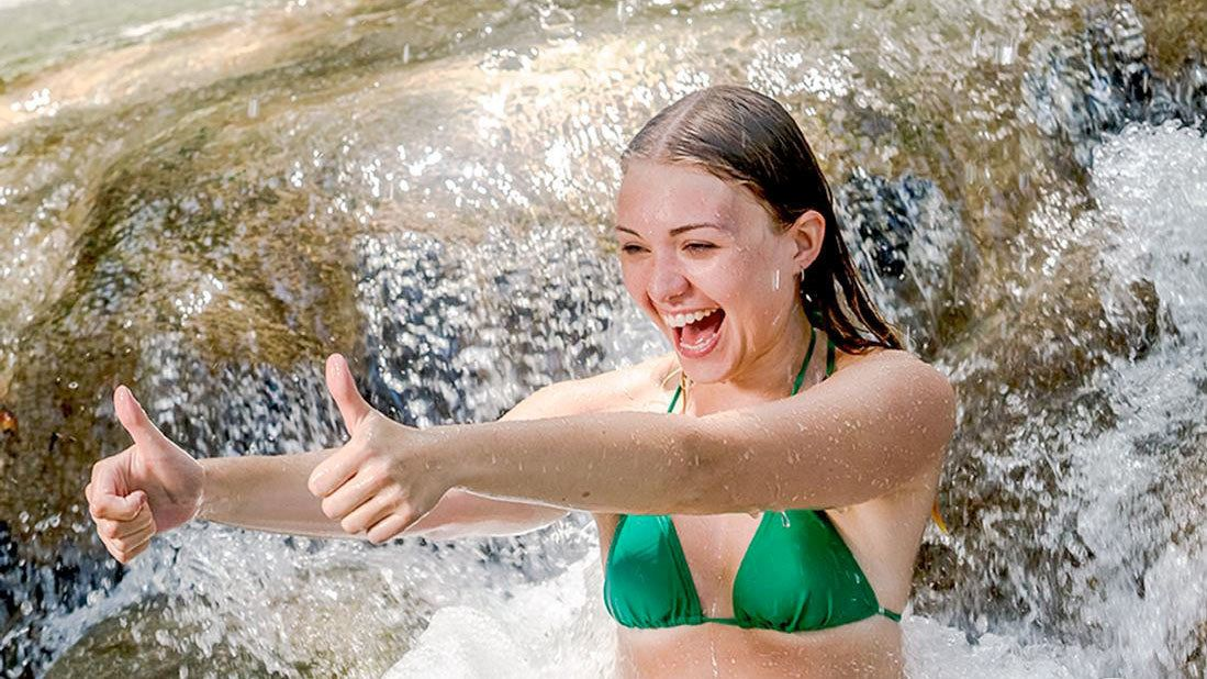 Woman giving a thumbs up and smiling on the Nine Mile and Dunns River Falls tour in South Coast, Jamaica