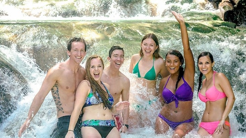 Group swimming in the waterfalls on the Nine Mile and Dunns River Falls tour in South Coast, Jamaica