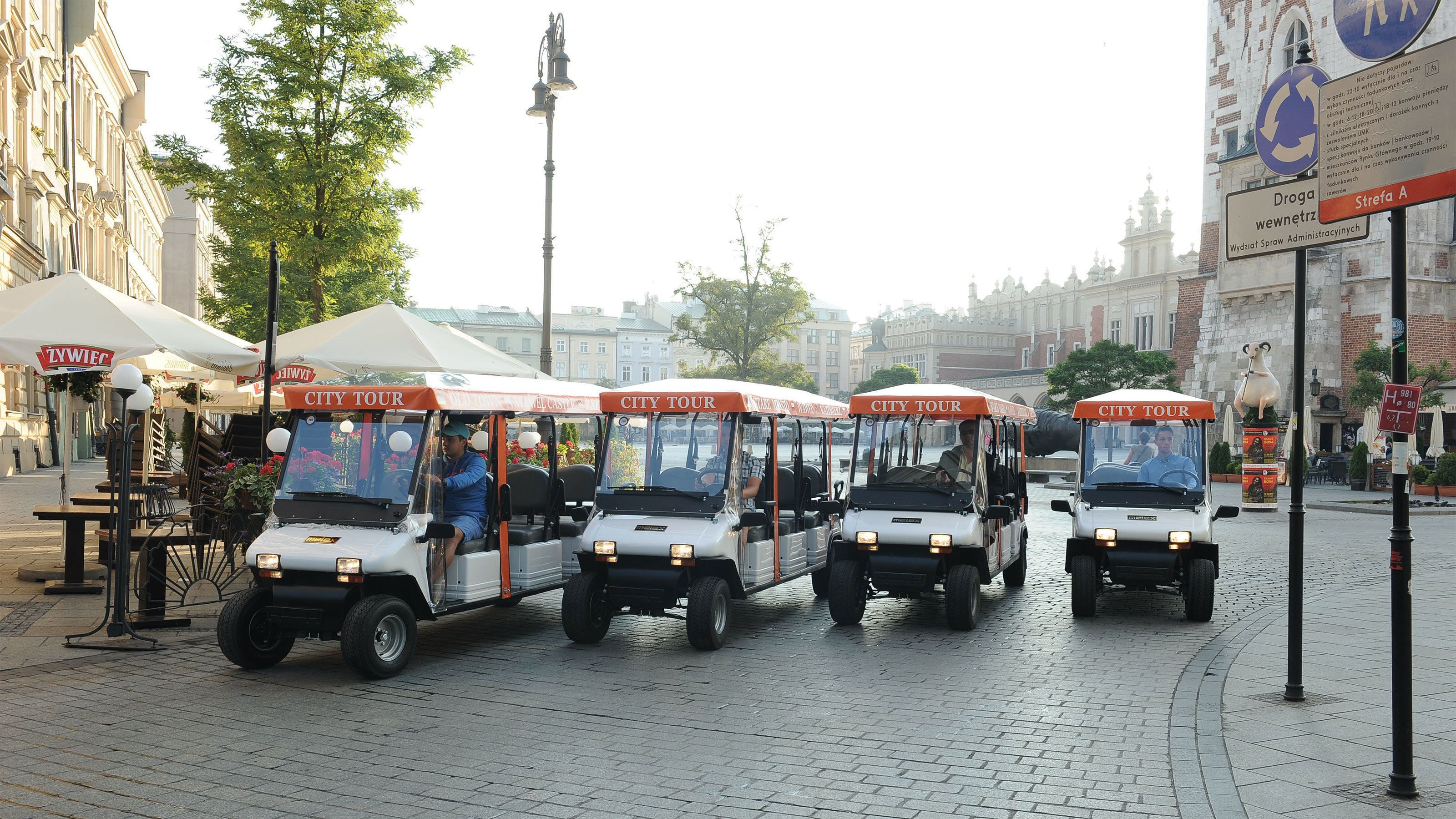 Eco vehicles in courtyard with several tourists on board.