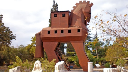 View of structure shaped like a horse surrounded by trees.