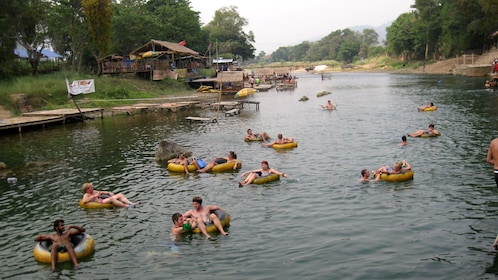 Several people on floats lounging in river.
