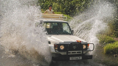 White Jeep driving through water.