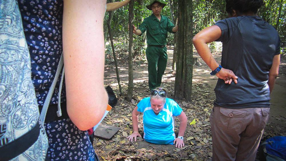 Woman entering Cu Chi tunnel while group members observe.