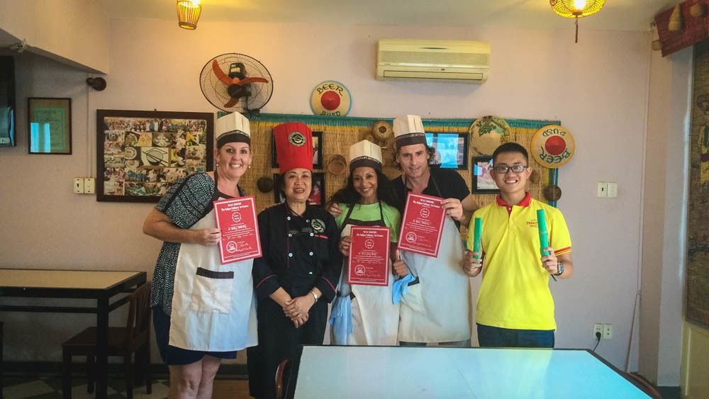 Group members posing with certificates of completion of cooking class.