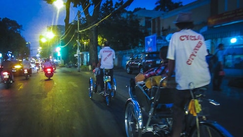 Cyclists on the streets of Saigon at night.