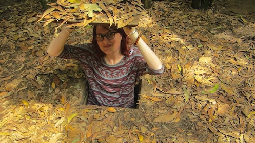 Tourist standing inside a hidden pit surrounded by leaves.