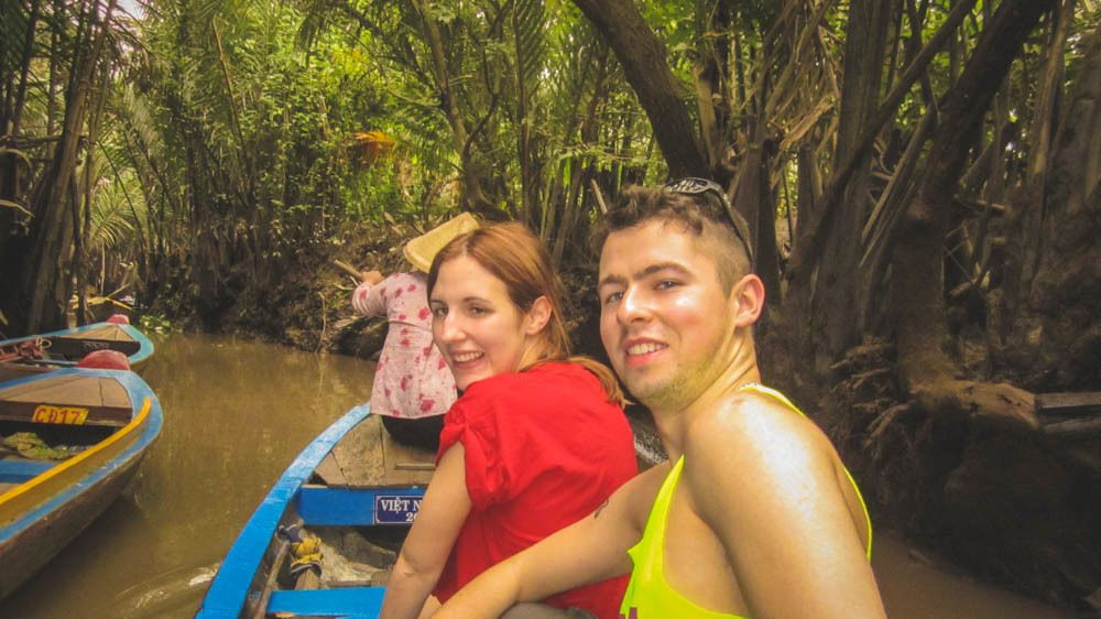 Tourists on boat, traveling by river in forest.