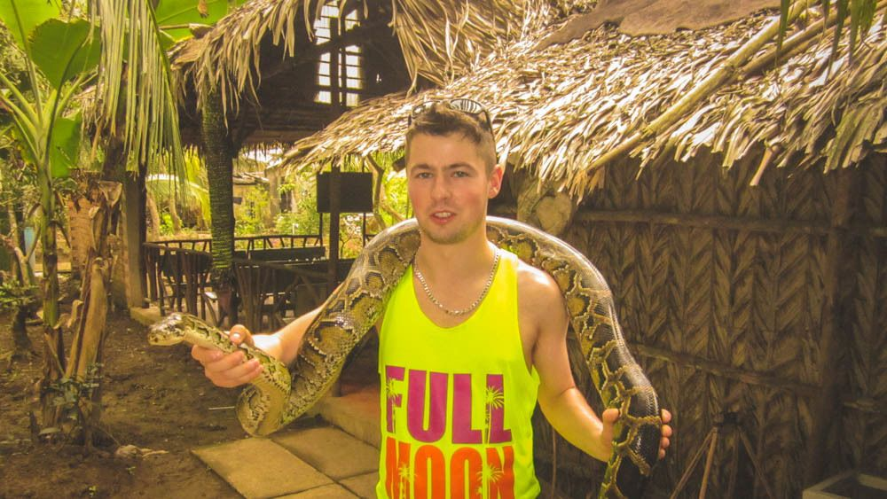 Tourist with giant snake over his shoulders.