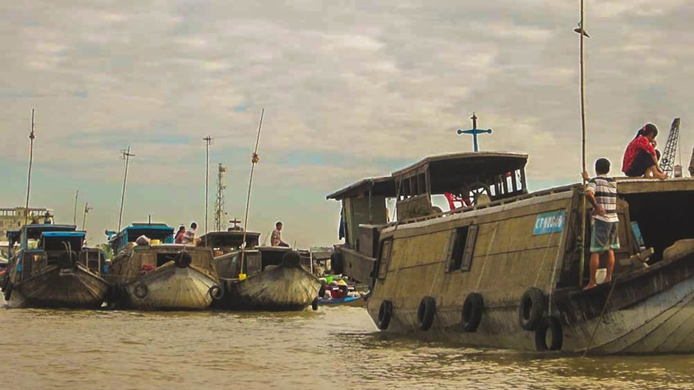 Show item 3 of 8. View of fishing boats in river during cloudy day.