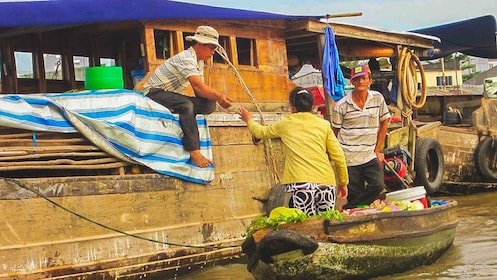 Woman buying fresh produce from boat market.
