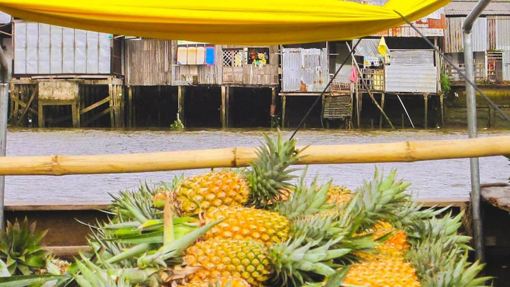 Show item 8 of 8. Whole pineapples loaded on to boat in market.