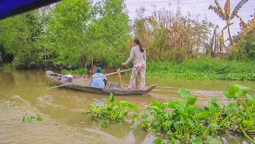 View of man and woman on row boat paddling through canal.