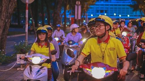 Tour group riding mopeds through the city at night.