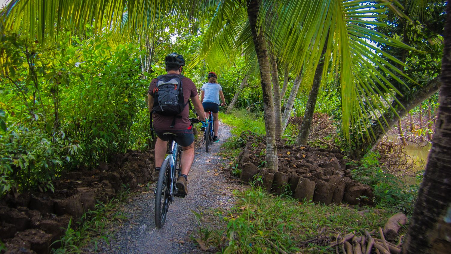 Male and female couple riding on bike path in Mekong Delta, shown from behind.