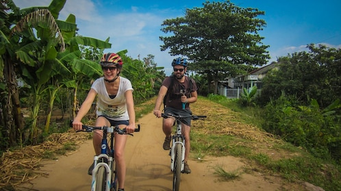 Couple riding on bike path in Mekong Delta.