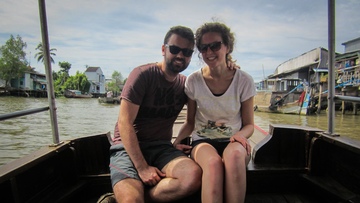 Male and female couple posing on boat in Mekong Delta.