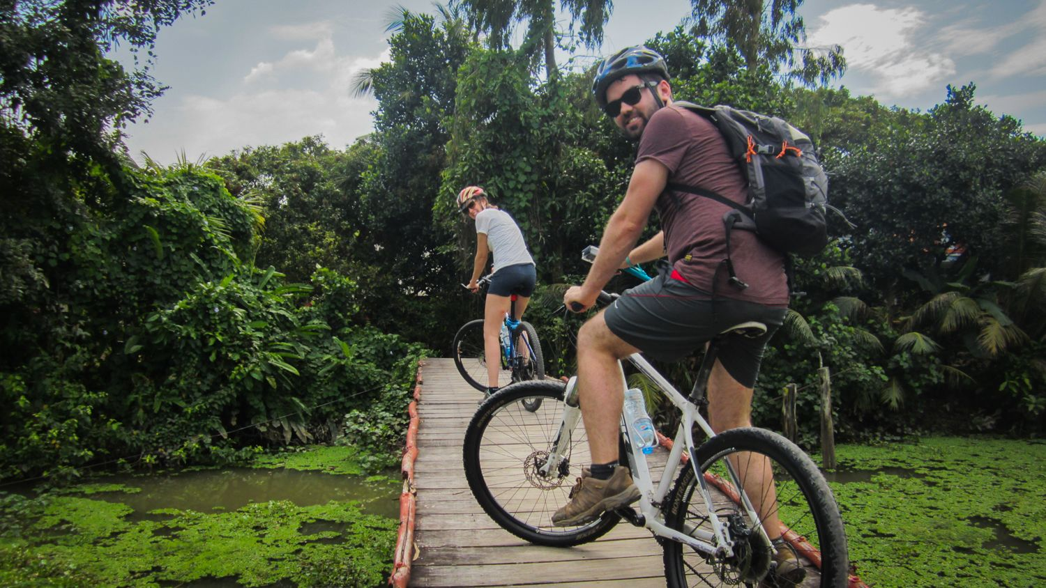 Male and female couple riding on bike path in Mekong Delta.