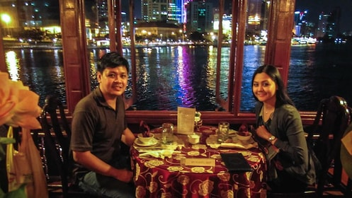 Couple having dinner by the waterfront at night, with few of city.