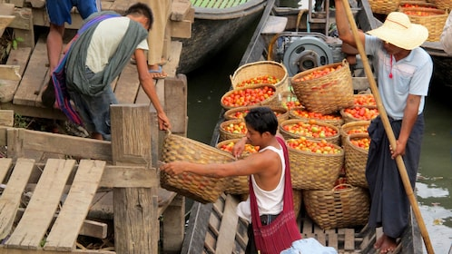 Locals moving fresh produce in baskets.