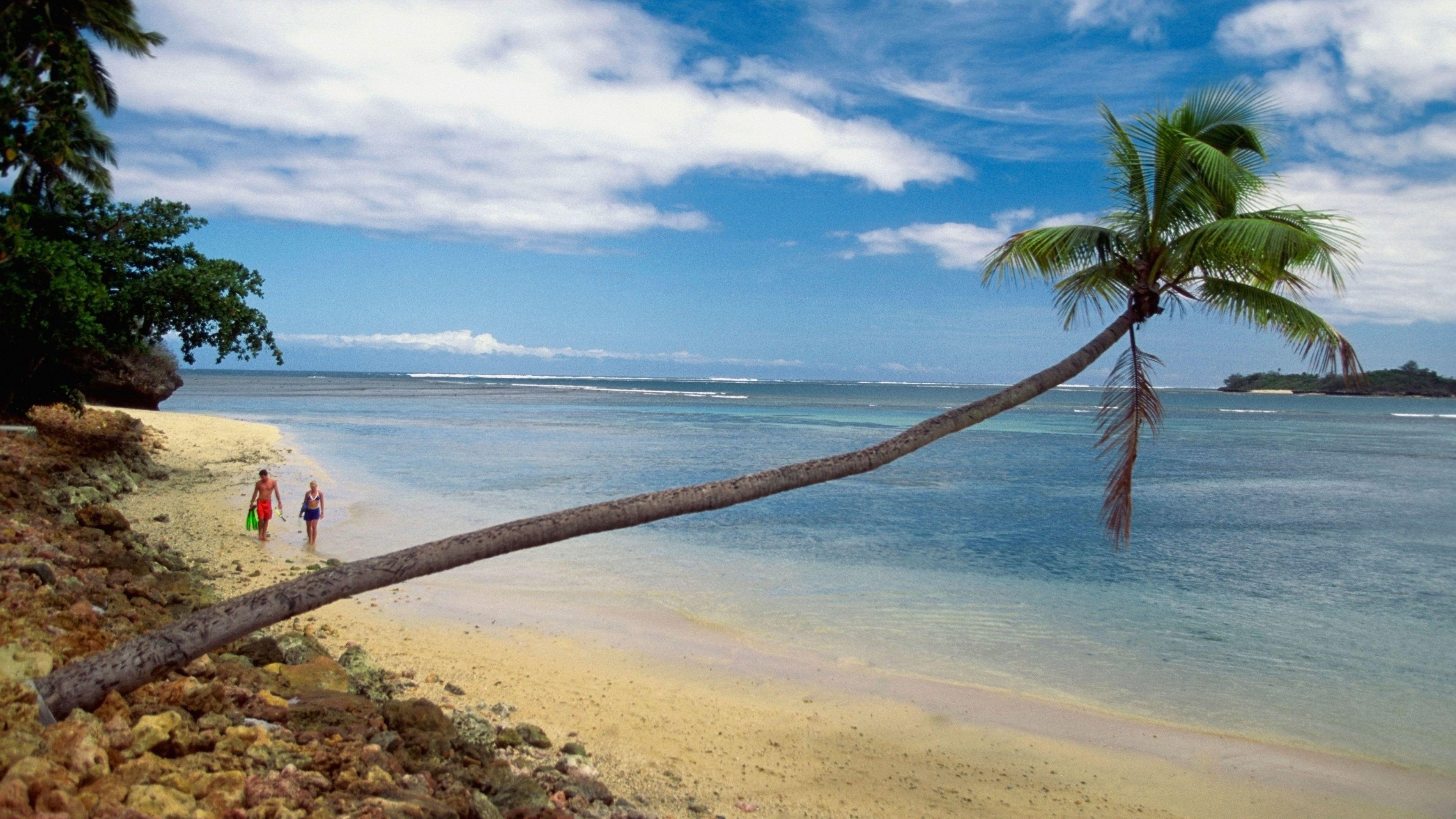 Couple with snorkeling gear walking along a beach in Fiji