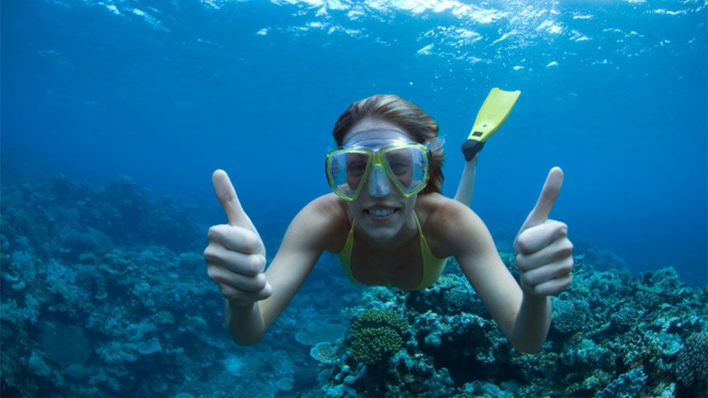 Snorkeling woman gives two thumbs up underwater in Fiji