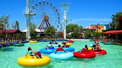 People in multicolored inner tubes with water cannons float in a large pool next to a ferris wheel