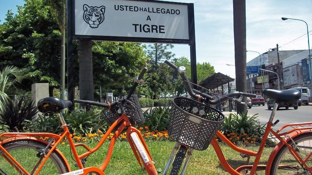 orange bicycle in front of Tigre sign