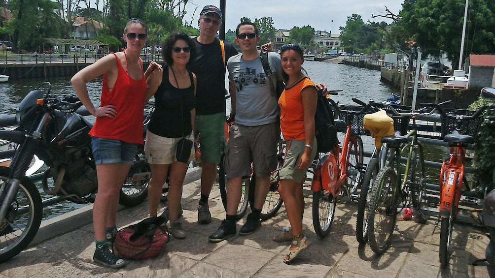 group posing with bicycles at river front