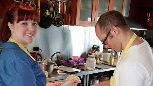 Two people in aprons cooking in a kitchen